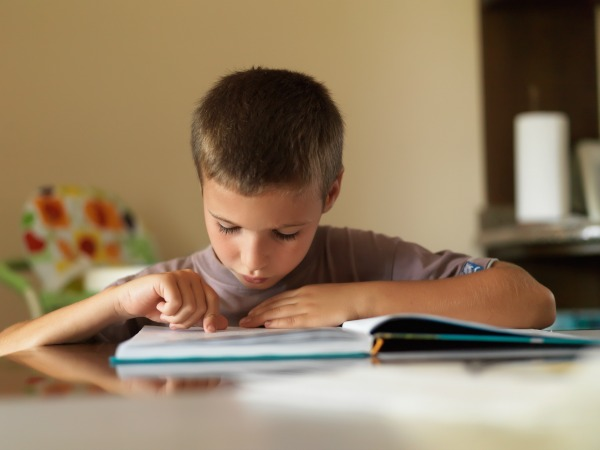 Portrait of focused boy reading a book while sitting at table at home.
